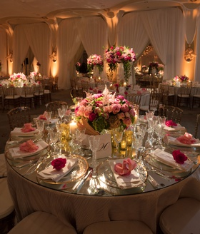 Wedding reception with round table drapery low pink centerpiece pink flower on top of plates