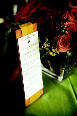 Wedding reception menu displayed on wood board with golden ribbon