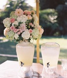 Outdoor wedding ceremony flower arrangement on wood table with drink dispensers filled with lemonade
