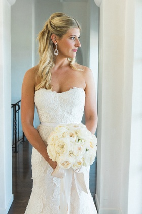 Blonde bride in strapless lace dress with white rose bouquet