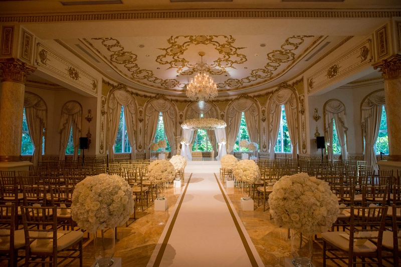 Wedding ceremony custom white and gold border aisle runner ballroom ornate white flowers gold chairs