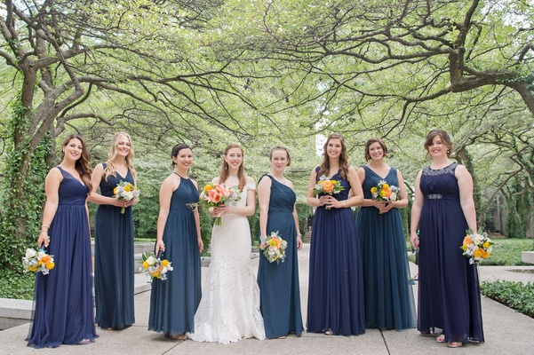 Bride in Romona Keveza wedding dress and bridesmaids in mismatched blue and teal wedding dresses