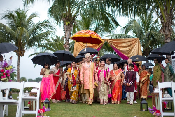 indian-american groom walks into ceremony with family, holding umbrellas due to rain