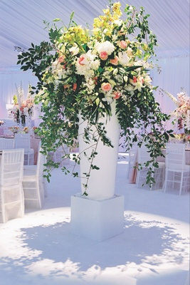 White riser filled with green leaves, pink roses and white flowers