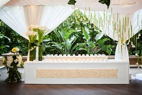 white wedding escort card table with cream flowers, white calla lily suspended from draped ceiling