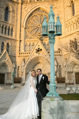 Bride in a Pnina Tornai dress with long-sleeve illusion neckline, veil, groom in black morning coat