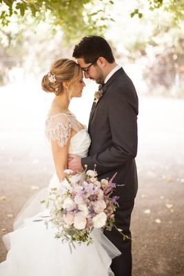 Couple in wedding attire touching foreheads