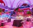 Weylin B Seymour's wedding reception with pink, purple, and greenery decorations with uplighting