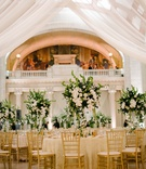 wedding reception columns gold chairs ivory linen greenery white flower centerpiece heatherlily