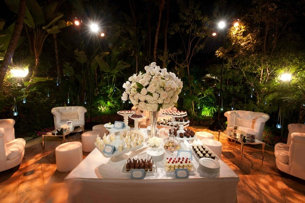 Plush white chairs around wedding dessert table