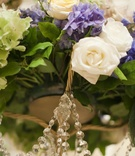 Wedding arrangement of purple, white, and green flowers with greenery and crystals