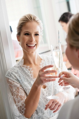 Bride toasting bridesmaid in lace robe with champagne flute and straw