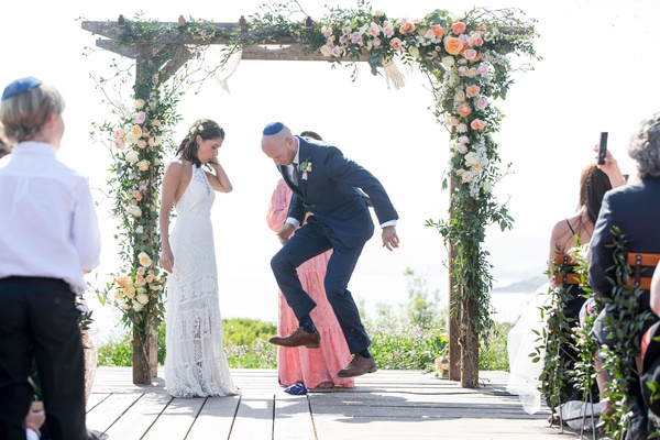 wedding ceremony rustic chic bride in lace dress with groom in navy suit wood arbor flowers greenery