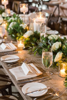 garland with white roses on long table with candles