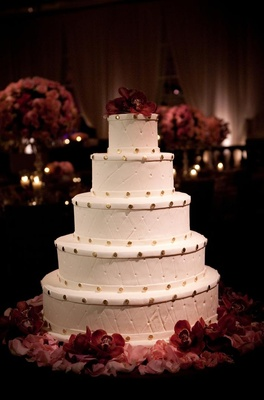 Round wedding cake with orchids and gold dots