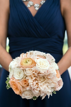 Bridesmaid in a sleeveless navy dress holds bouquet of white roses, peach ranunculuses, roses, pink