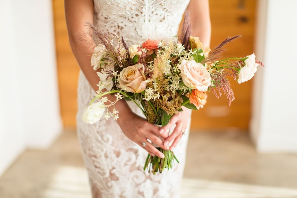 rustic bridal bouquet with roses in ivory and orange and grasses