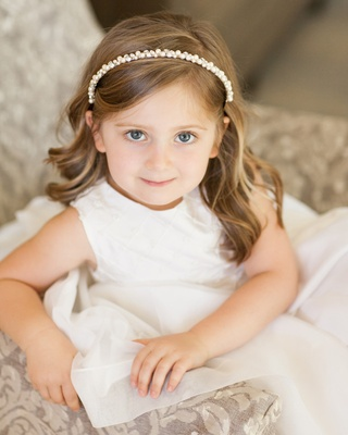 Flower girl in white dress on chair with pearl headband