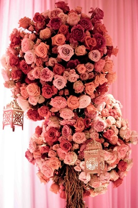 Moroccan lanterns hanging from large rose flower arrangements