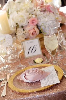 Wedding reception place setting with pink napkin folded into rosette on clear charger with golden