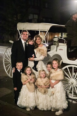 flower girls with fur wraps, ring bearers in tuxedos, horse-drawn carriage at wedding
