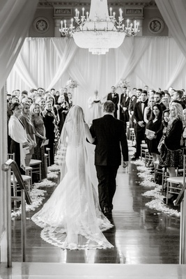 Black and white photo of bride being escorted by father of the bride down aisle back view biltmore