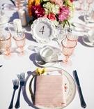 pink wine glasses, pink napkins, pink tableware, table number