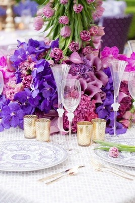 Wedding reception table with versace champagne flute and wine glass, china with purple pattern