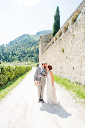 bride in sleeveless wedding dress groom in grey suit and fedora italy wedding venue destination