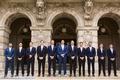 groom and groomsmen in suits in varying shades of dark blue