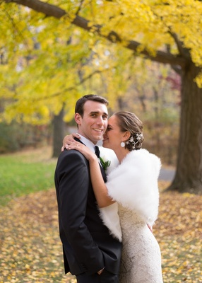 Bride in a lace Monique Lhuillier gown and stole hugs groom in a black tuxedo