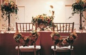 Floral garlands on backs of bride and groom dinner chairs