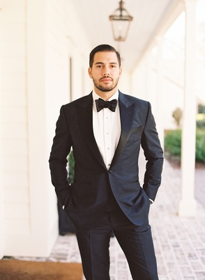 Groom in tuxedo and bow tie with hands in pockets on porch wrap around south carolina lowcountry