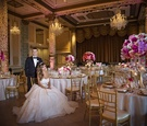 bride in alyne ball gown with large belt sits in chair in front of groom in tuxedo in drake hotel
