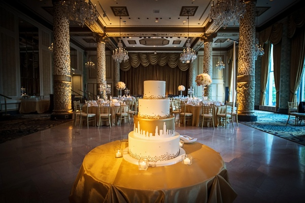 four-tiered wedding cake with gold dots and white chicago skyline