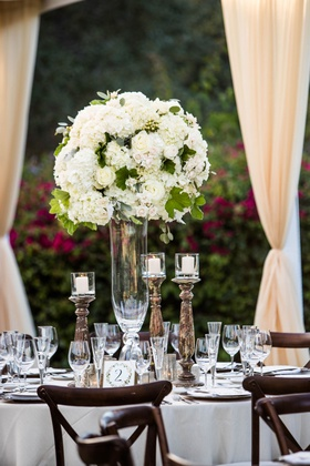 wedding reception tall centerpiece white hydrangea roses greenery wood chairs candles