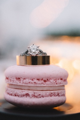 Wedding rings on pink French macaron