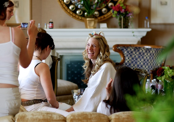 Bride with bridesmaids in all white in bridal suite