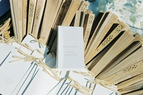 Tan fans were provided next to white wedding programs