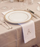 Gold-rimmed china plate with monogrammed napkin