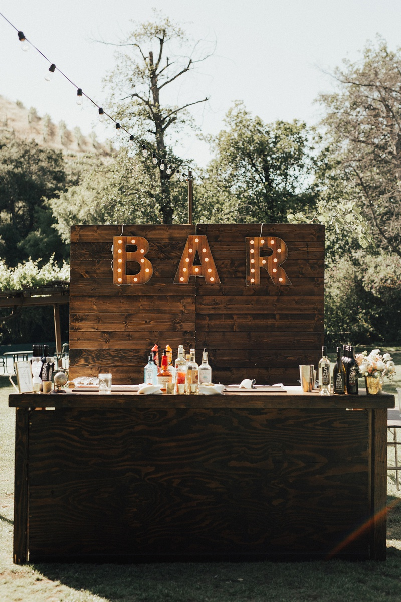 outdoor wedding with wooden bar setup with BAR marquee lights