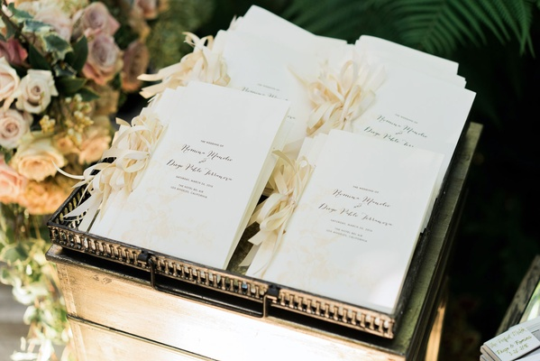 Ceremony programs with champagne ribbons on side and elegant script in metal tray