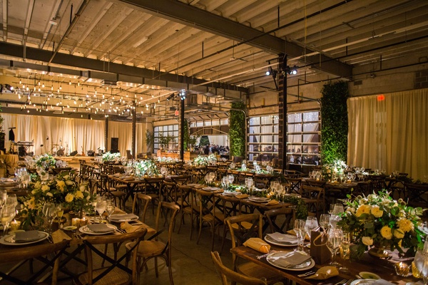 Warehouse wedding venue rustic decor wood tables green white centerpieces light bulb dance floor