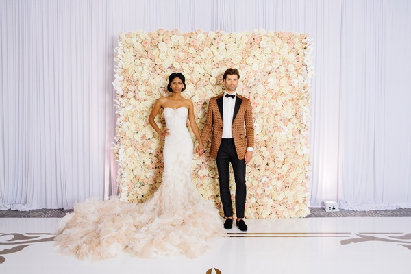 bride in inbal dror mermaid gown, groom in bronze patterned tuxedo jacket, ivory & blush floral wall