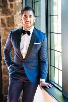 Wedding getting ready groom in navy suit with black lapels and velvet bow tie white cuffs pocket