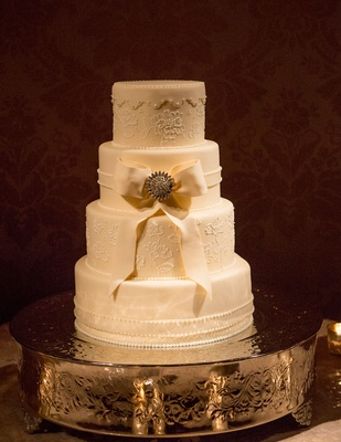 four layer ivory wedding cake with fondant ribbon and jewel