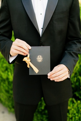 black ceremony program with gold monogram tied with gold ribbon