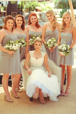 Jenna Reeves in wedding dress armchair with five bridesmaids in short grey cocktail dresses