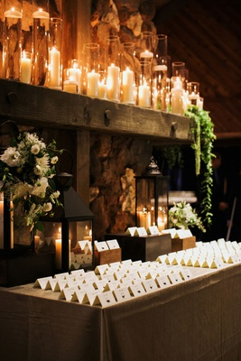 escort cards on table in front of lanterns and lots of candles in tall hurricanes
