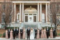 Wedding party in front of venue with bridesmaids and groomsmen